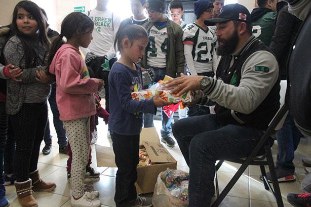 El coach Miguel Muela entregando regalos a los niños